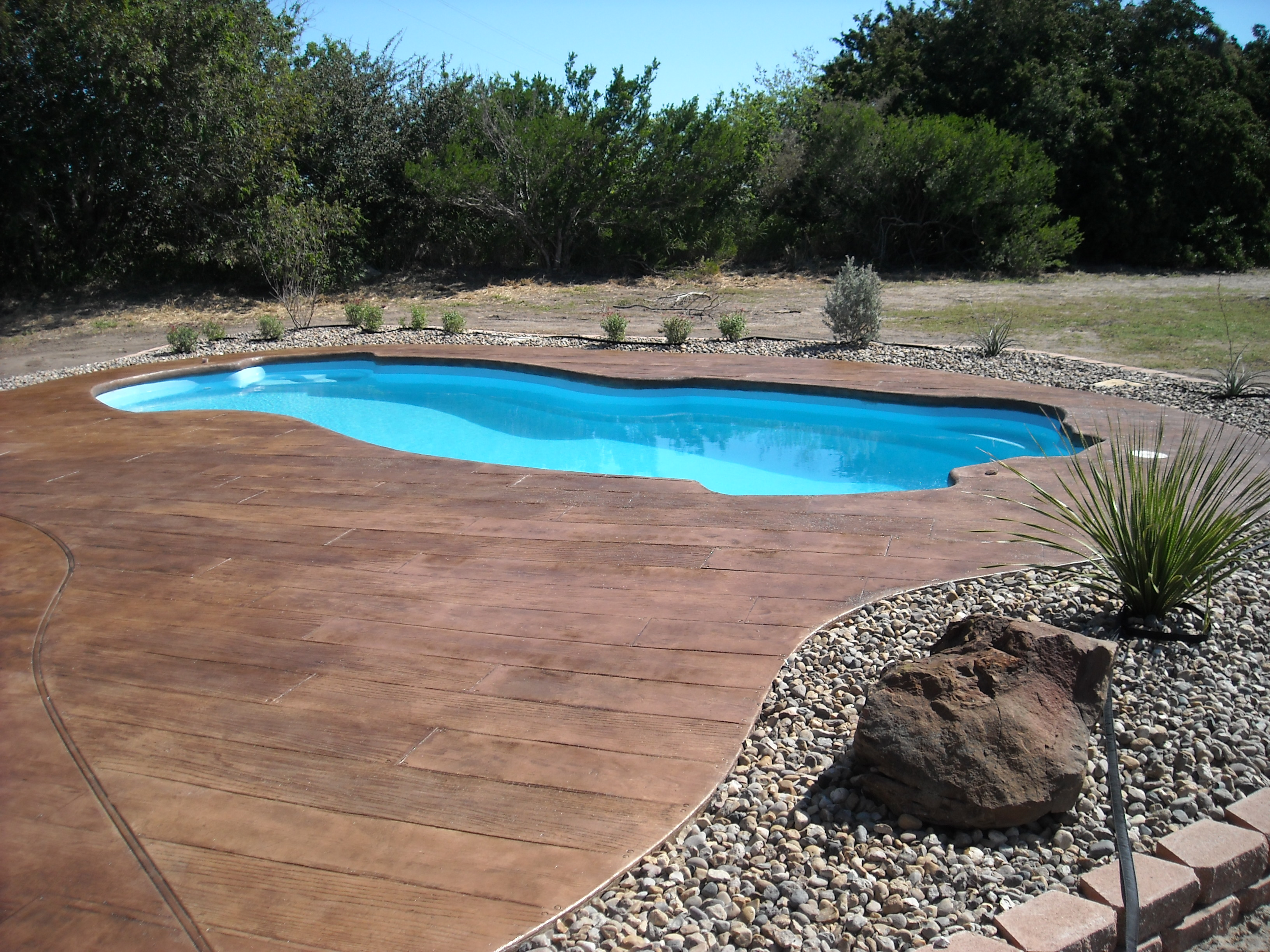 Backyard swimming pool in Corpus Christi with design concrete around it.