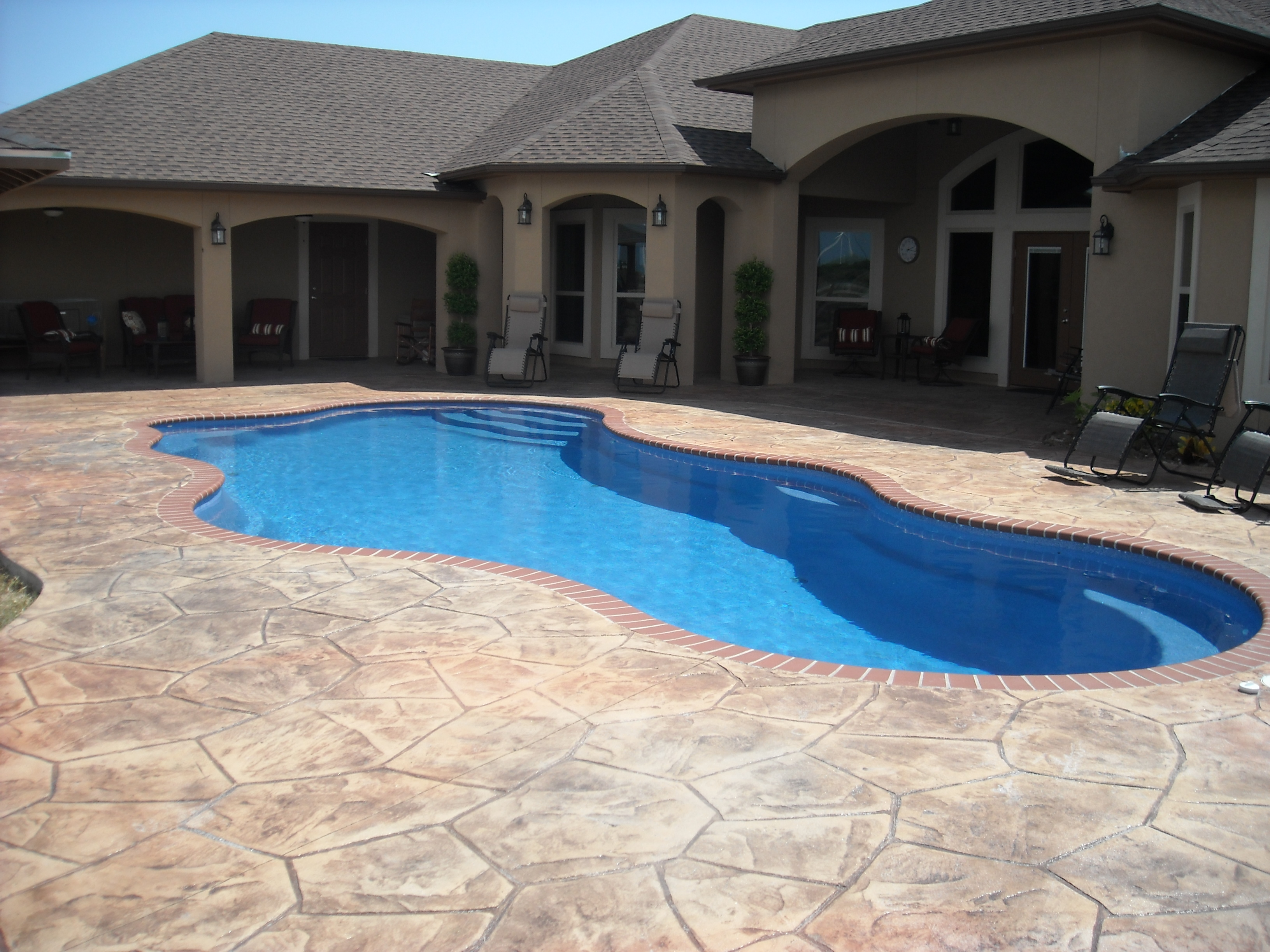 Swimming pool in backyard with decorate concrete surrounding it