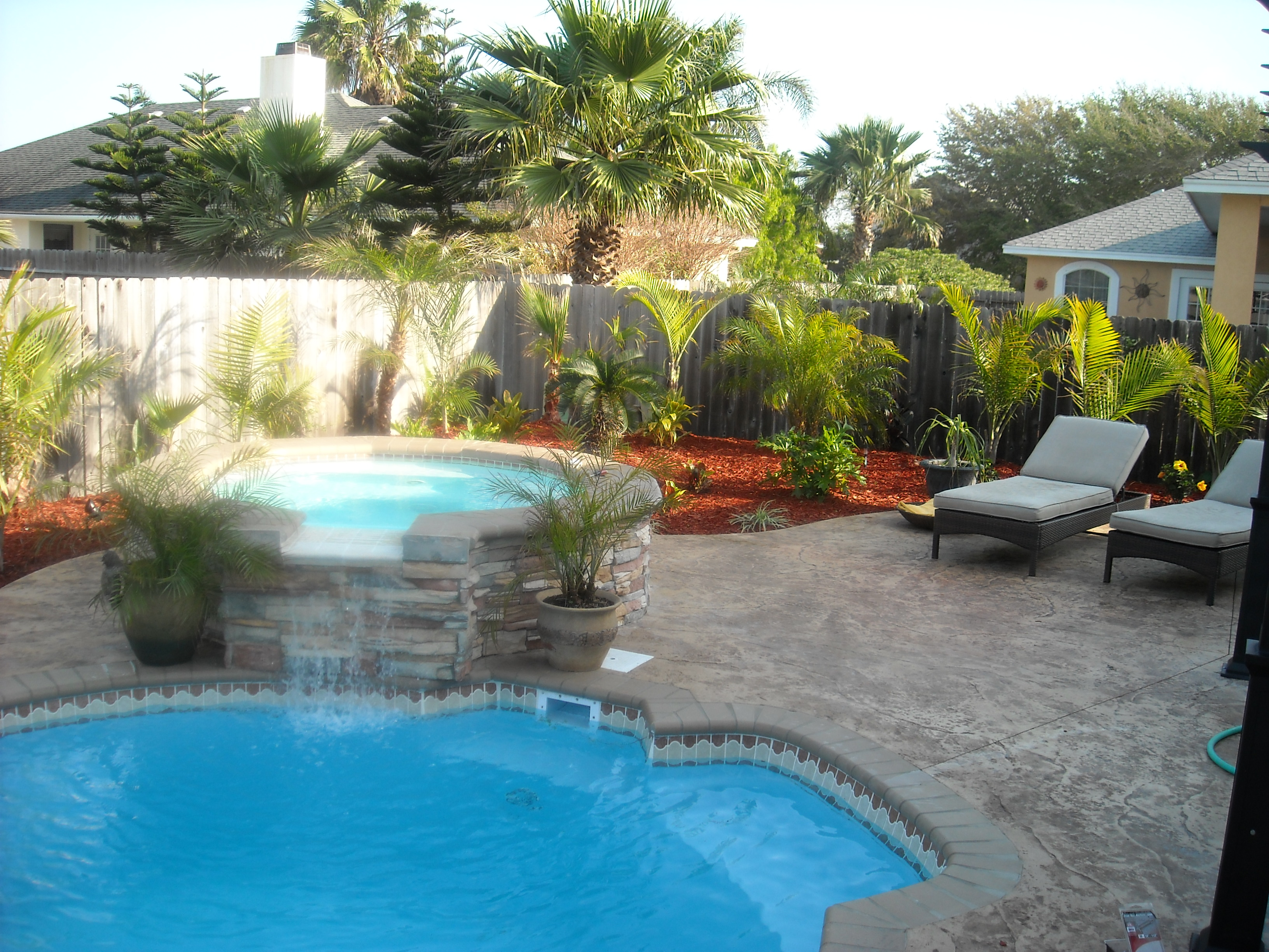 Fiberglass pool with water feature, decorative concrete, and landscaping