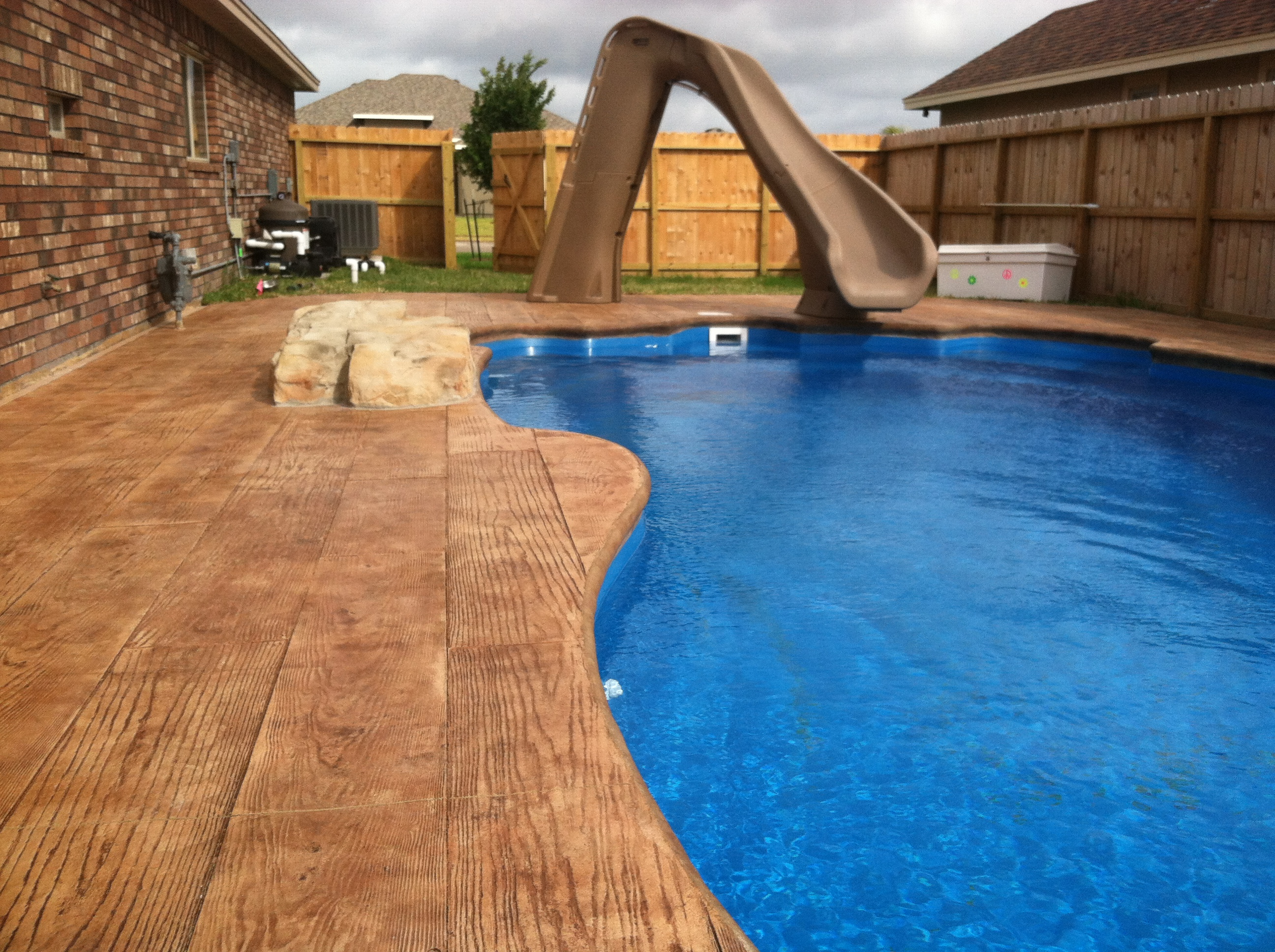 Pool with decorative concrete and a slide.