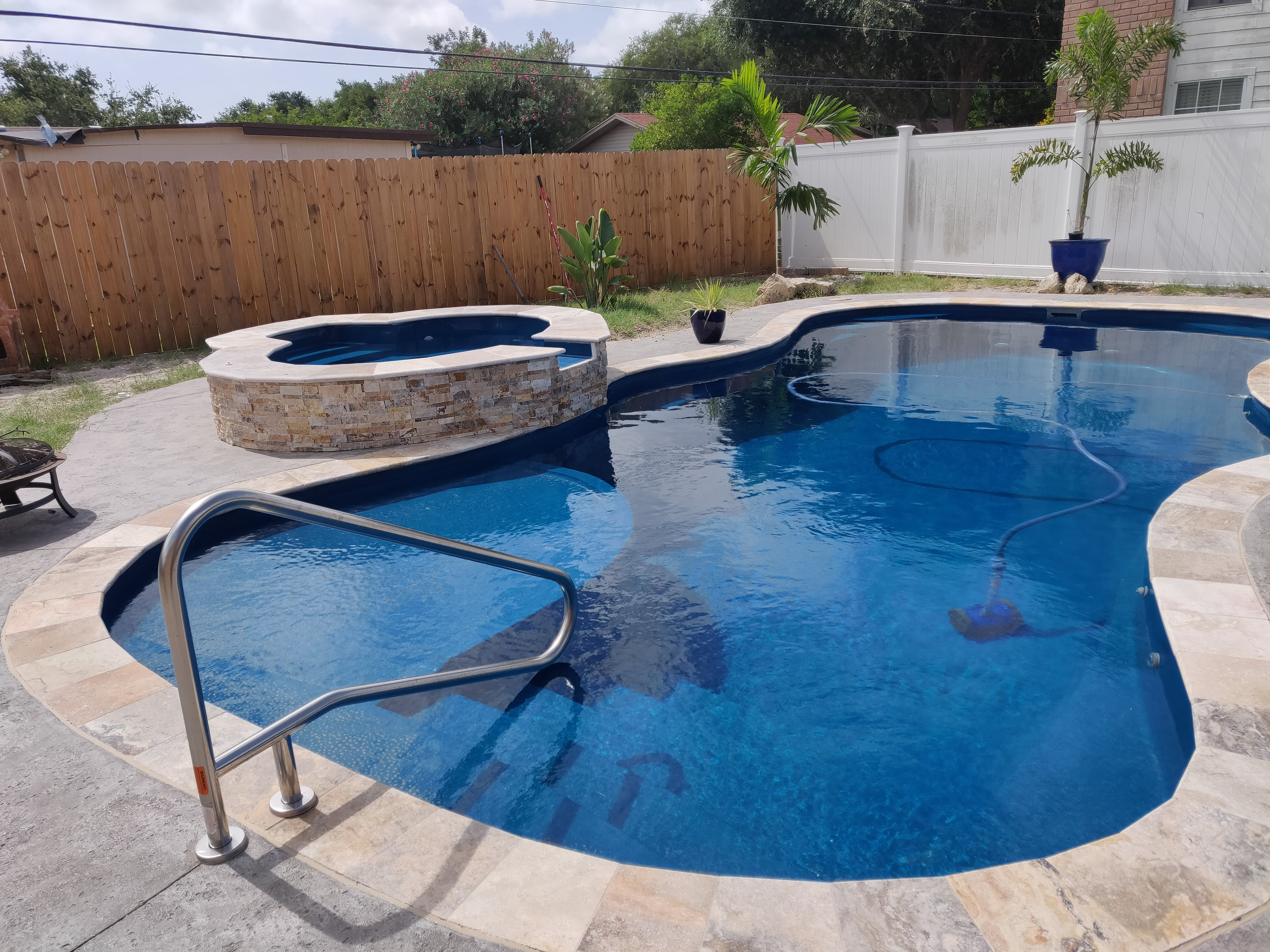 In-ground pool in Corpus Christi with a water feature and stone.
